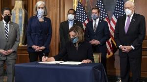 Nancy Pelosi signing articles of impeachment against Donald Trump