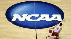 Wisconsin's Traevon Jackson dribbles past the NCAA logo