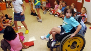 young girl in a wheelchair in a school hallway