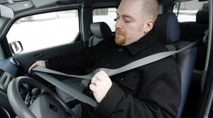 Driver checks length of seat belt in car
