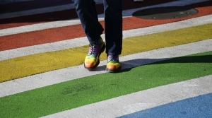 A pedestrian in rainbow shows in a rainbow crosswalk