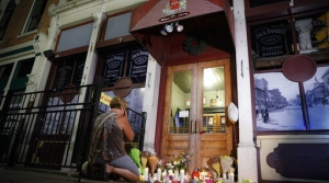 Mourners visit a makeshift memorial outside Ned Peppers bar following a vigil in Dayton, Ohio.