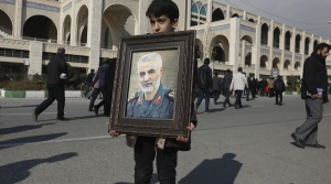 A boy carries a portrait of Gen. Qassem Soleimani