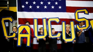 "Attendees spell out ""CAUCUS"" during a campaign event"