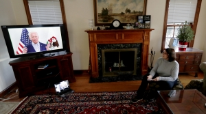 A Chicago woman watches a virtual campaign event on her TV