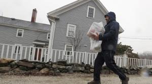 An Instacart worker delivers groceries in the rain