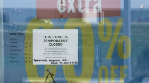 A closed sign hangs on the door outside J. Crew store in Wauwatosa