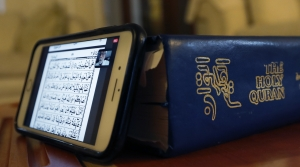 A phone rests against the Quran