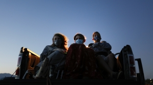 Three people sit in the back of a pick-up truck wearing masks to watch a film at a drive-in movie theatre.