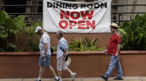 "People walk past ""Dining Room Now Open"" sign"