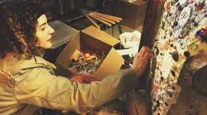 A woman presses an object into a mortar-covered surface as part of the collage art process.