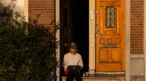 A woman sits on a stoop while using her computer.