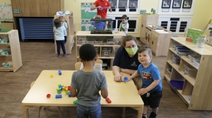 Masked childcare workers assist children in daycare