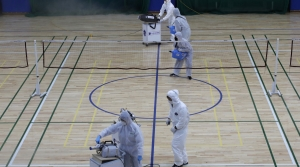 Workers spray disinfectant as a precaution against the coronavirus at an indoor gymnasium in South Korea.
