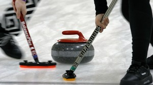 Members of a curling club sweep ahead of the rock