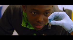 A teen sickle cell patient looks at test tube containing CRISPR