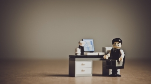 A lego figure sits at his toy desk.