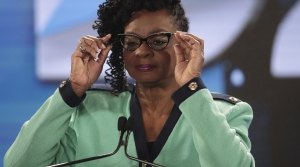 Representative Gwen Moore adjusts her glasses at the podium at the 2020 DNC