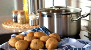 a basket of rolls next to a pot on a stove