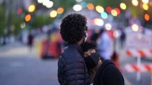 A masked couple hugs in Black Lives Matter Plaza