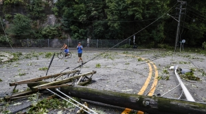 Debris from trees and power lines lie in a road brought down by Hurricane Isaias
