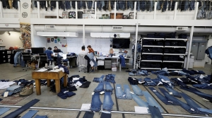 Several pairs of jeans are laid out on the floor of an open studio work space.