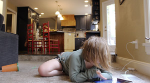 A child uses an ipad on the floor of her home from school work