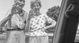The photographer's parents wave bye in their driveway as she drives away