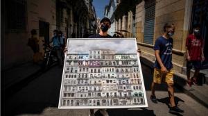 A man holds a photo of an NFT he created