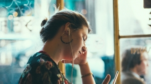 a woman looks down at her phone on public transit