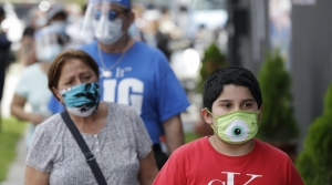 People waiting in line wearing masks