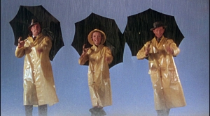 Three actors from the movie hold black umbrellas and wear yellow raincoats in the opening scene.