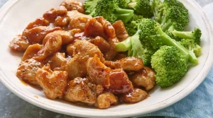 Sticky chicken alongside a serving of steamed broccoli in a white bowl.