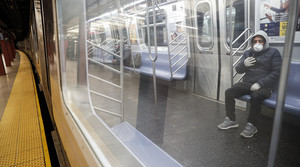 Subway rider wears gloves and mask in early days of pandemic