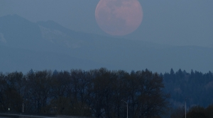 A lone car passes as the so-called pink supermoon rises, Tuesday, April 7, 2020, as seen from Tacoma, Wash.