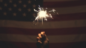 A hand holds a sparkler in front of the American flag