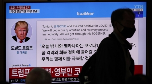 A masked person walks past a screen displaying President Trump tweet