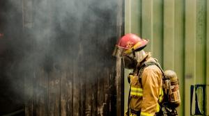 A firefighter gazes at a fire