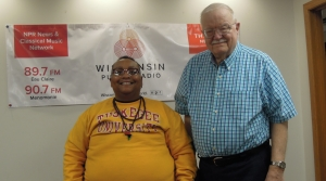 Le'Trice Donaldson and Jim Oliver standing in front of a Wisconsin Public Radio sign.
