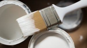 paint brush and cans of white paint