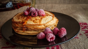 Pancakes with raspberries and maple syrup.