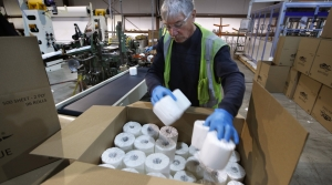 Worker fills a box with toilet paper at the Tissue Plus factory
