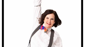 Paula Poundstone holding on to the top part of the frame surrounding her photo