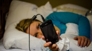 Woman holding smartphone in bed