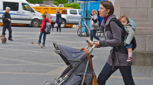 A mother walks down the street pushing one child in a stroller and carrying another on her back