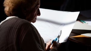 Woman using scissors to cut hand print out of paper