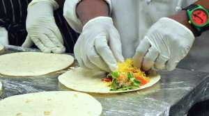 Person learning how to fold a burrito