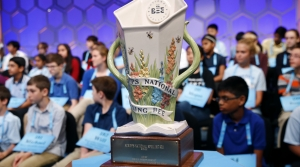 The Scripps National Spelling Bee trophy sits in front of competitors