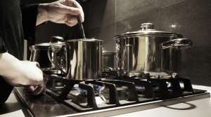 person stirring pot on stove