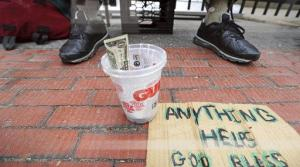 Panhandling sign sits next to cup with money
